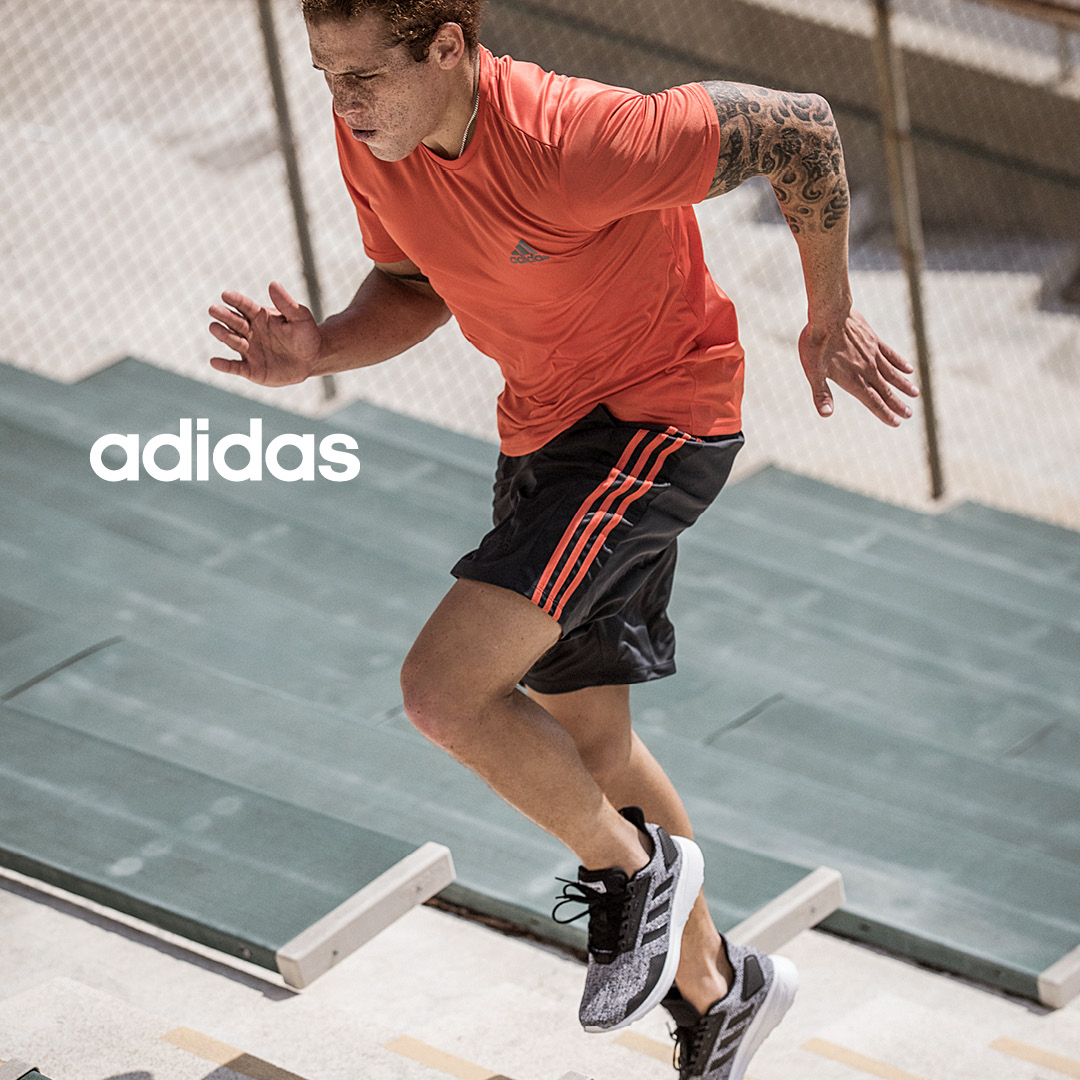 man running stairs wearing adidas athletic shoes