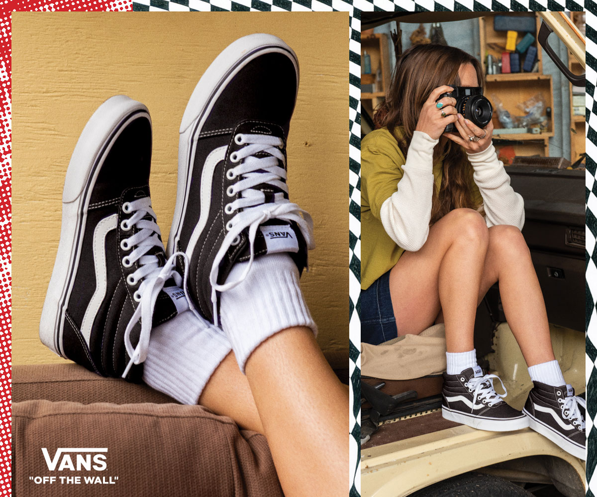 cool young woman wearing black and white mid-top vans sneakers