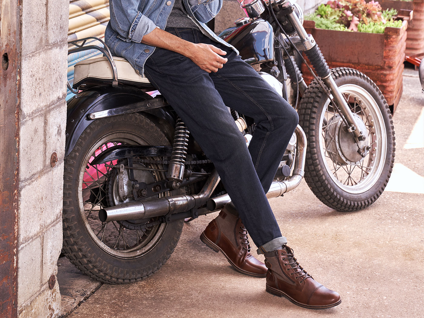 cool man leaning on a motorcycle wearing stylish boots